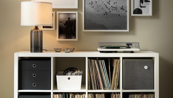 Une lampe de table TONVIS et un tourne-disque sur une étagère KALLAX blanche remplie de vinyles et d'autre rangement.
