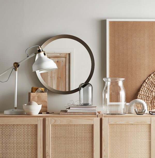 Une lampe de travail blanche RANARP, des livres, un miroir rond et deux vases sur le dessus d'une armoire en bois IVAR avec portes.