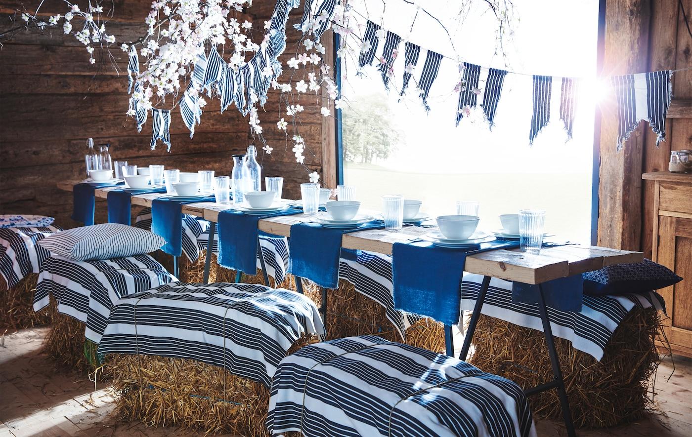 Une longue table dans une grange en bois avec de la vaisselle bleue et blanche, et du tissu à rayures en banderole et attaché sur des balles de foin servant de sièges.