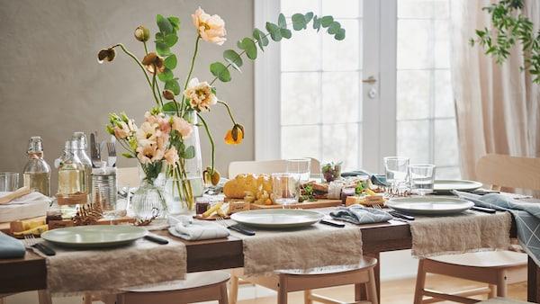 Une longue table MÖRBYLÅNGA dressée de façon festive avec du tissu AINA, des assiettes FÄRGKLAR, des fleurs dans des vases et différentes décorations.