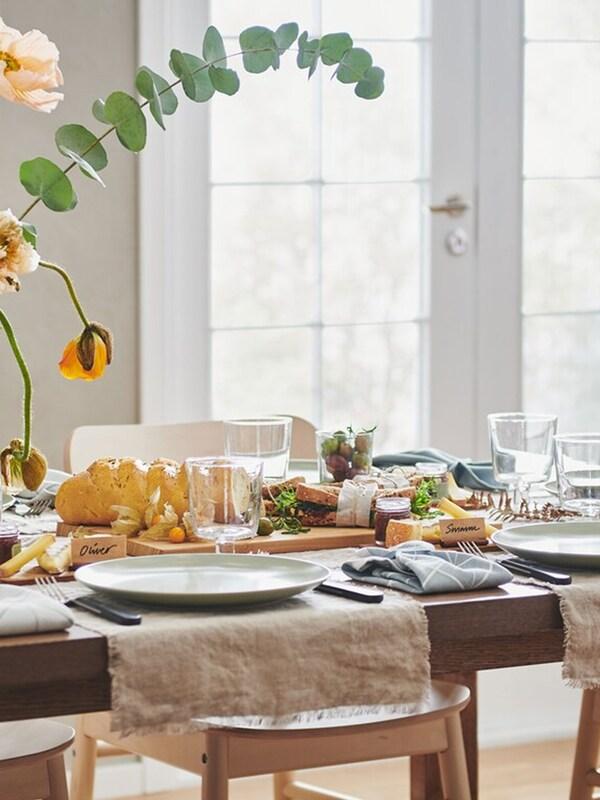 Une longue table MÖRBYLÅNGA mise pour un événement festif avec des bandes de tissu AINA, des assiettes FÄRGKLAR, des vases de fleurs et différentes décorations.