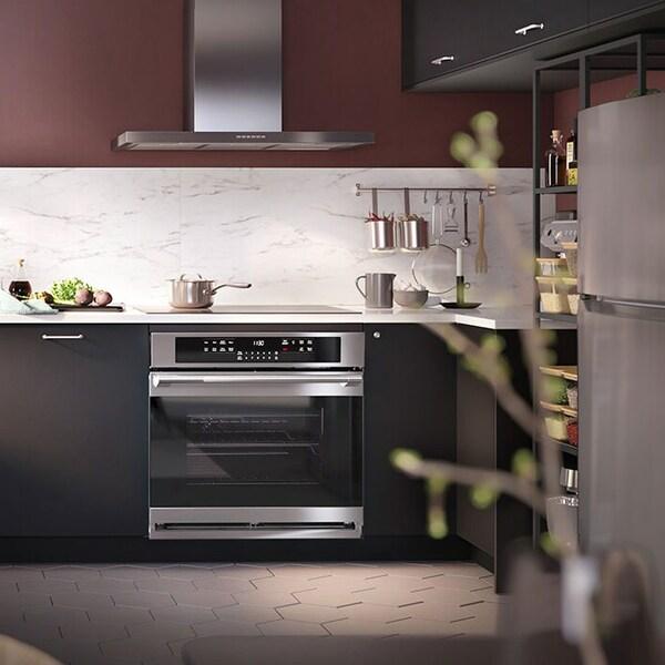Une magnifique cuisine moderne avec des armoires foncées et des électroménagers en acier inoxydable.