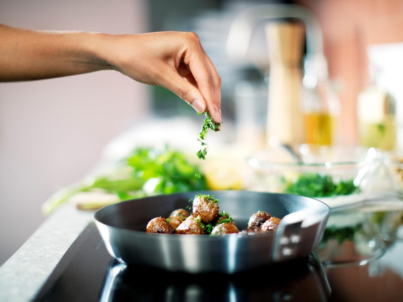 Une main assaisonne des boulettes végétales HUVUDROLL dans une poêle IKEA 365+.
