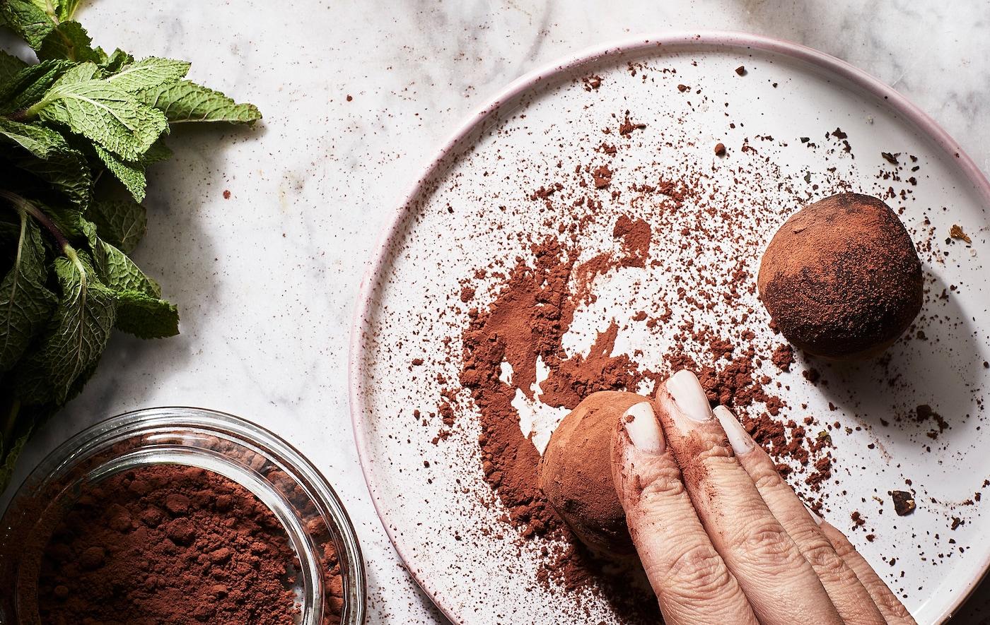 Une main roulant une truffe ronde de la taille d'une boulette dans de la poudre de cacao sur une petite assiette plate, des feuilles de menthe fraîche sur le côté.