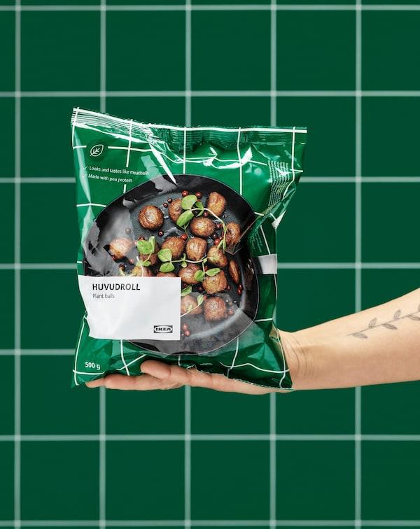 Une main tendue tenant un paquet en plastique, fermé, de boulettes végétales HUVUDROLL. On voit un mur de carrelages verts à l'arrière-plan.