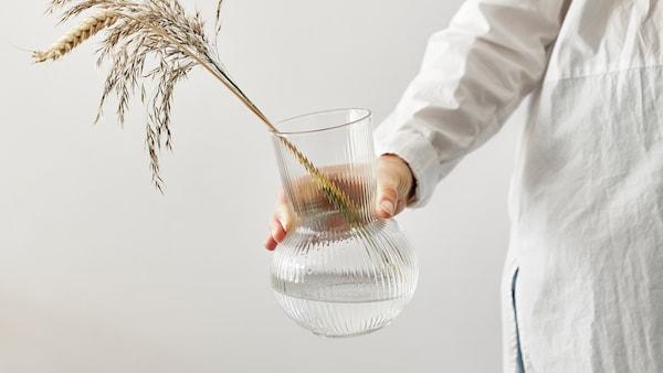 Une main tendue tient un vase PÅDRAG en verre transparent avec une tige de blé et des graminées séchées.