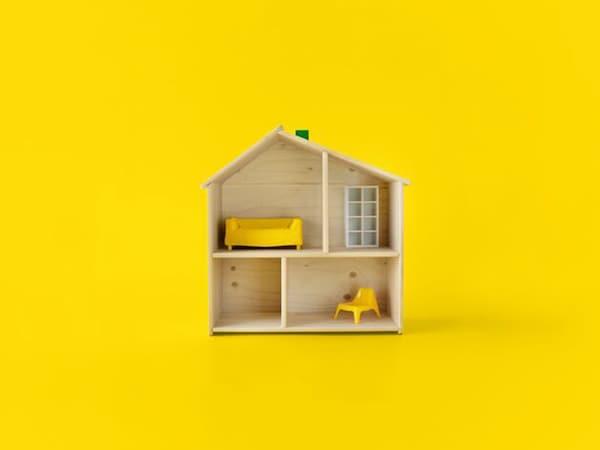 Une maison de poupée en bois avec des meubles IKEA à l'intérieur.