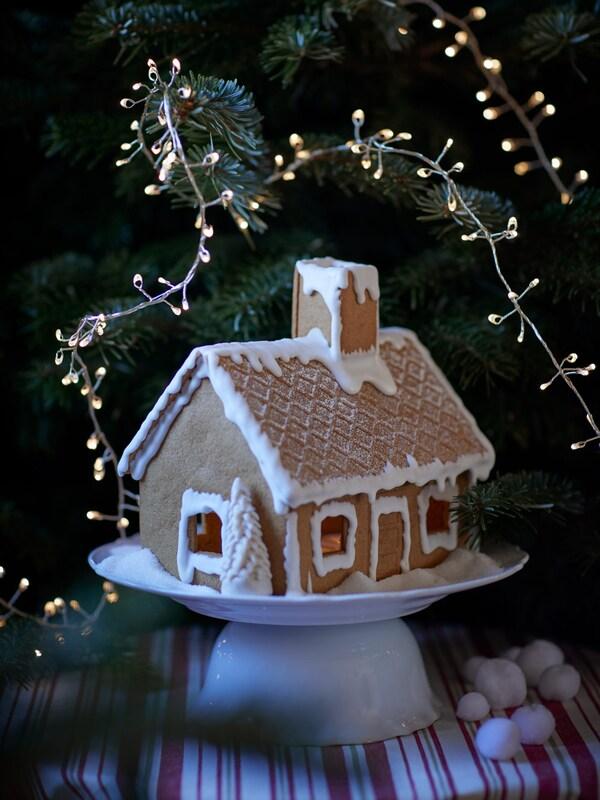 une maison en pain d'épices devant un sapin de Noël