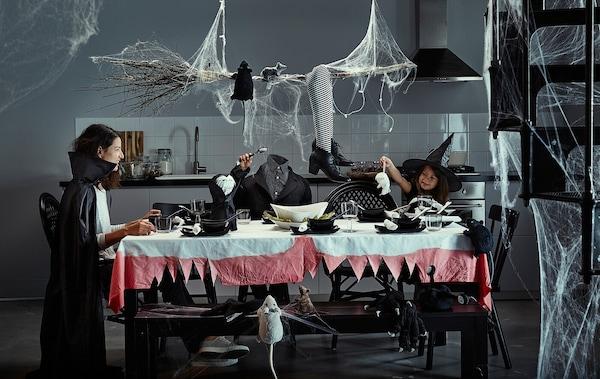 Une mère et ses enfants assis à une table décorée pour l'Halloween avec des toiles d'araignées, des costumes et des décorations effrayantes.