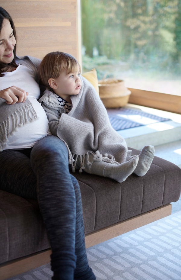 Une mère et un jeune enfant enveloppés dans un plaid en laine gris OMTÄNKSAM, assis tout près l'un de l'autre sur un canapé.