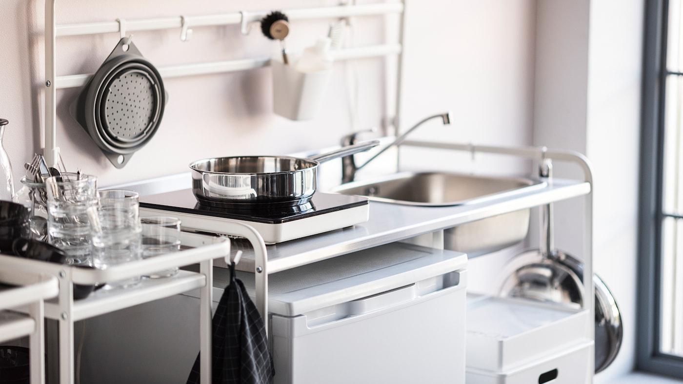 Une mini cuisine blanche avec une table de cuisson à induction portable et un petit réfrigérateur.