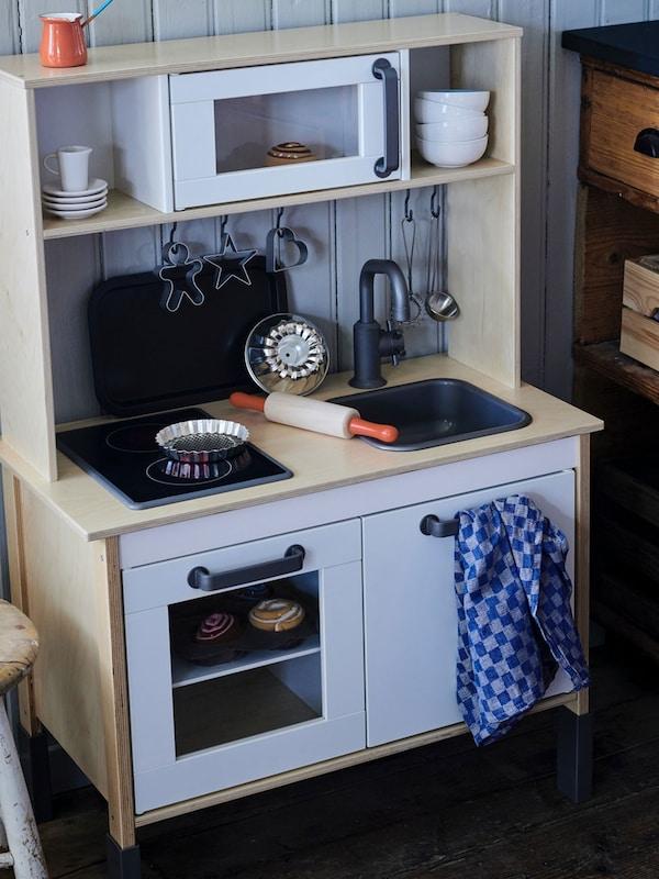 Une minicuisine DUKTIG en bouleau avec des accessoires de cuisine et des pâtisseries.