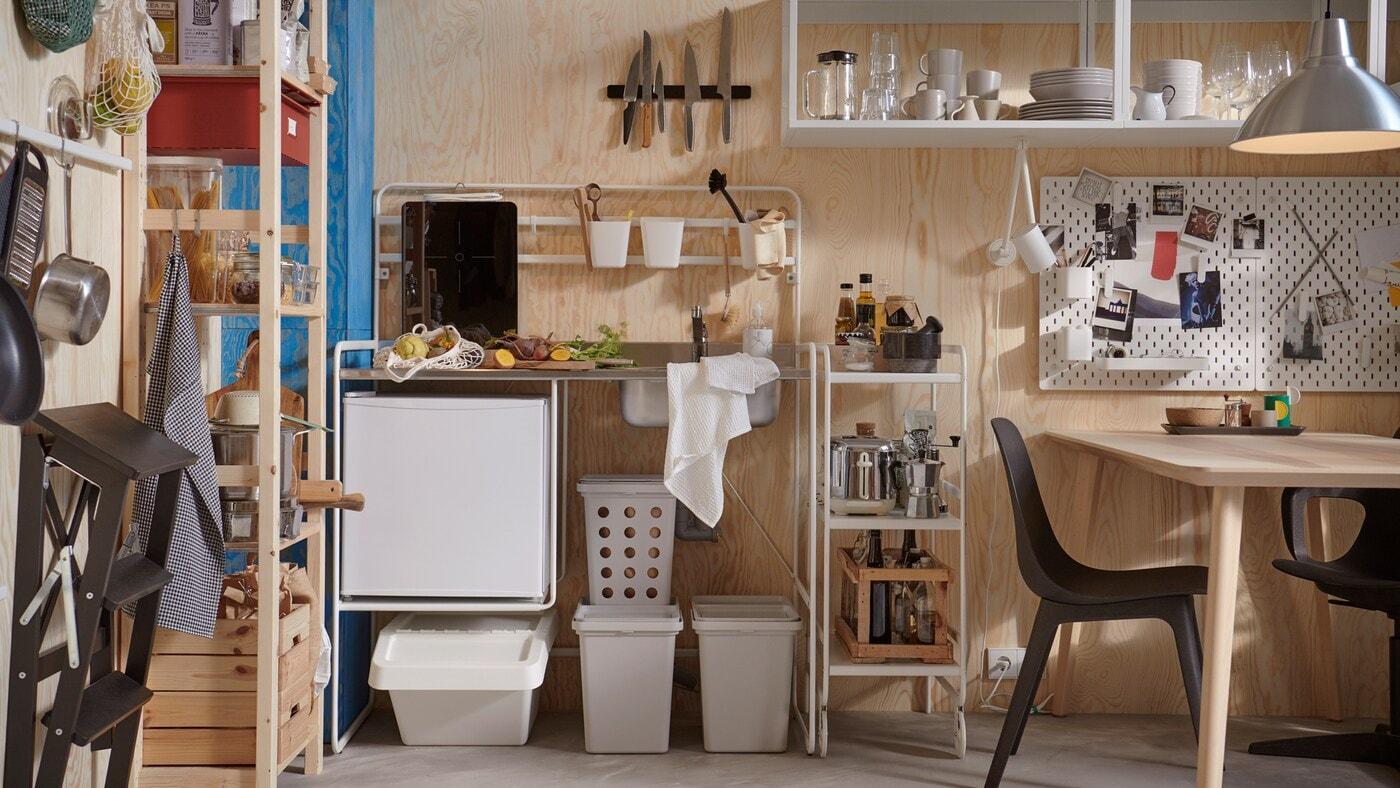 Une minicuisine SUNNERSTA avec accessoires, une étagère IVAR, et une table et des chaises dans une petite pièce aux murs en contreplaqué.
