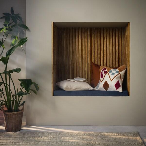 Une niche en bois avec des coussins colorés pour s'asseoir dans un mur blanc.