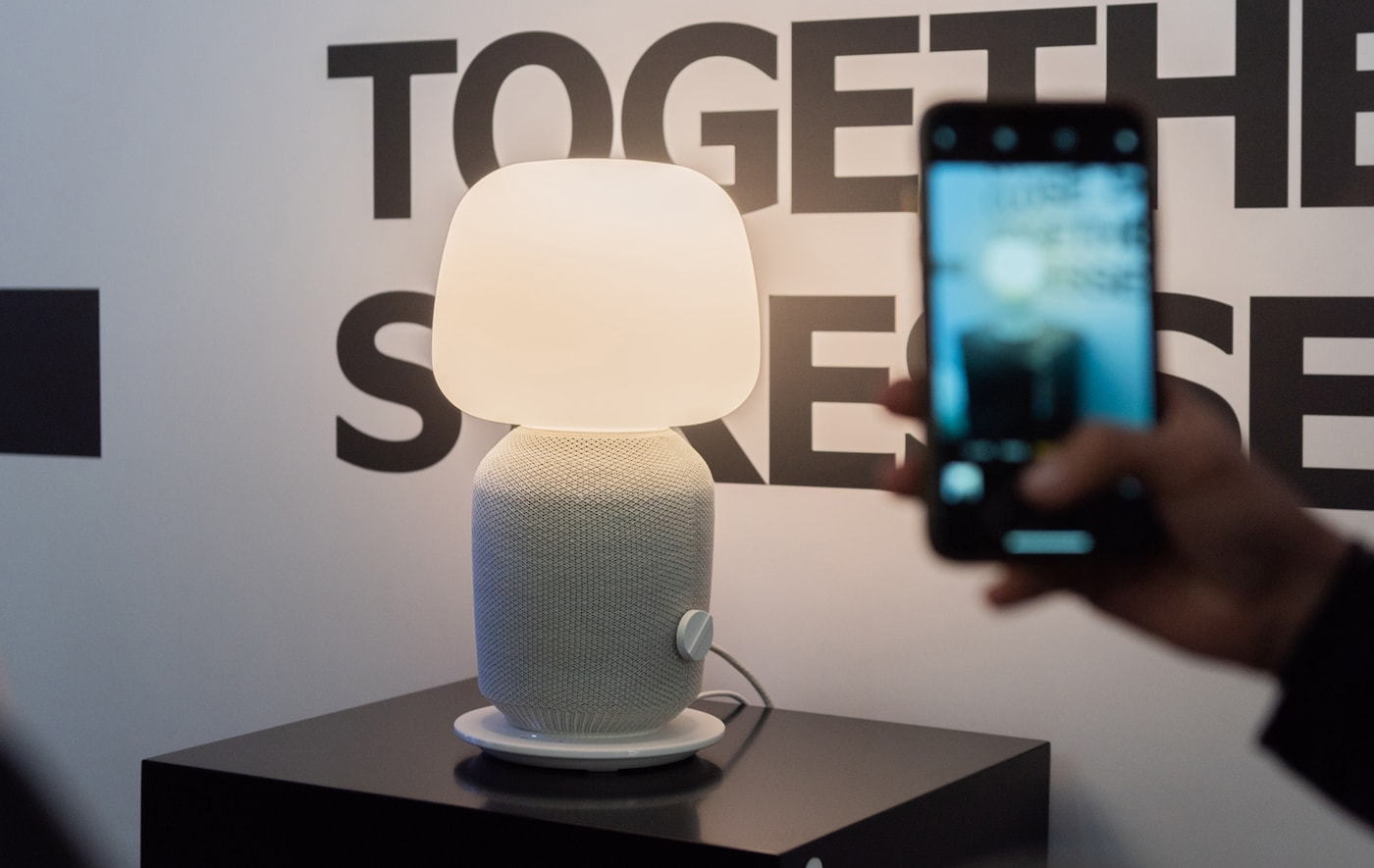 Une nouvelle enceinte SYMFONISK sous la forme d'une lampe de table posée sur un meuble et photographiée à côté d'un texte.