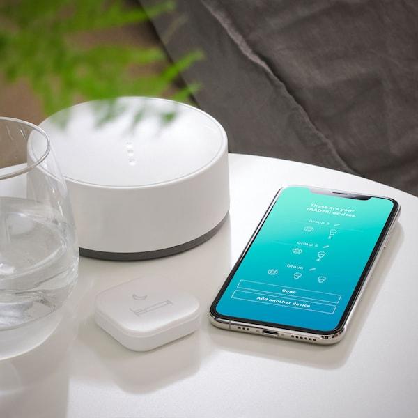 Une passerelle TRÅDFRI sur une table blanche près d'un téléphone intelligent montrant l'appli Home smart.