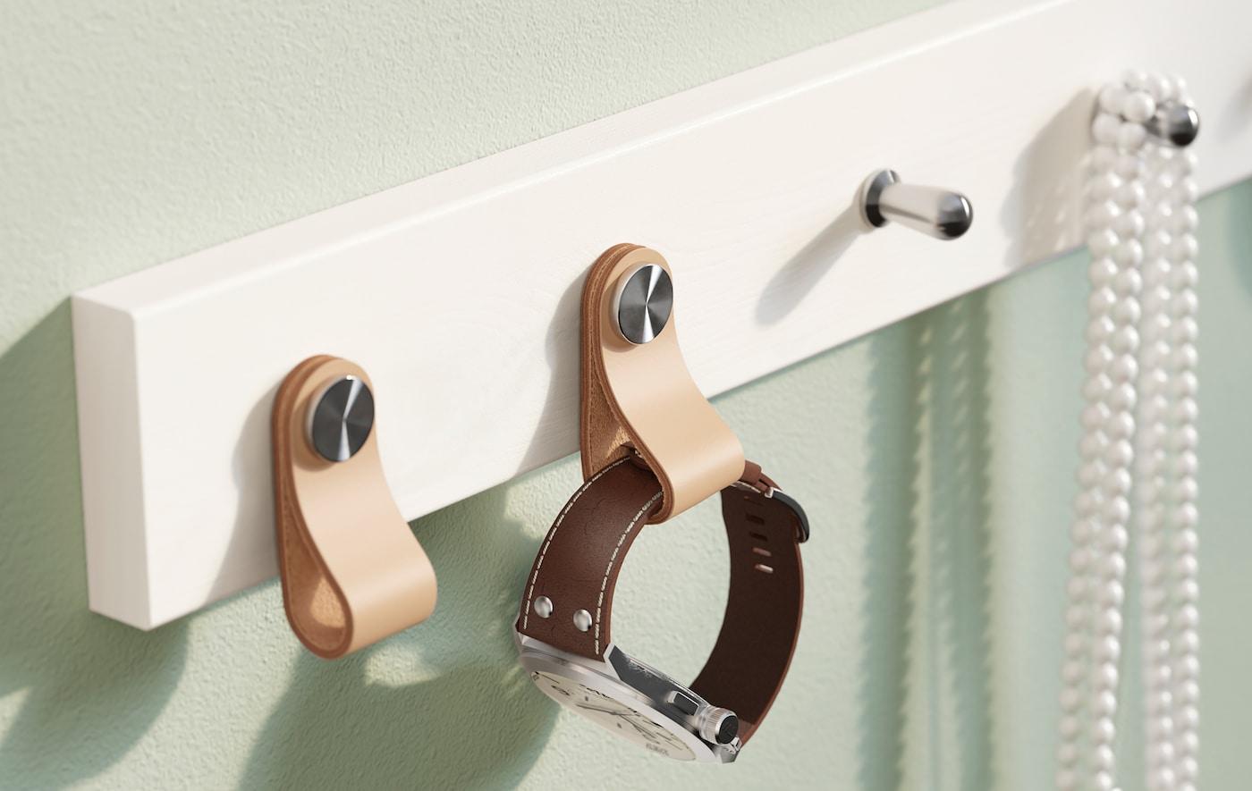 Une patère IKEA LURT blanche pour 6 boutons à laquelle une montre et quelques perles sont suspendues.