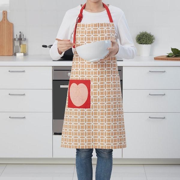 Une personne dans une cuisine qui porte un tablier à motifs rouges de la collection SOLGLIMTAR et qui tient un bol à mélanger.
