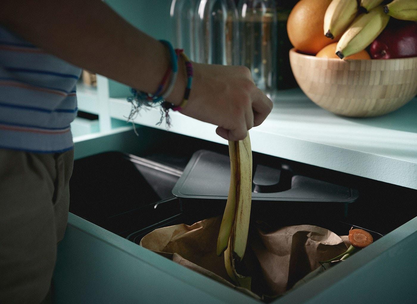 Une personne portant des bracelets laissant tomber une peau de banane dans une poubelle de recyclage IKEA VARIERA, dans un tiroir de cuisine.