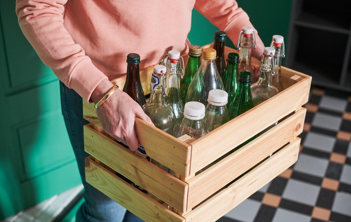 Une personne se déplaçant dans un hall en portant une caisse en bois KNAGGLIG pleine de bouteilles de verre et de plastique.