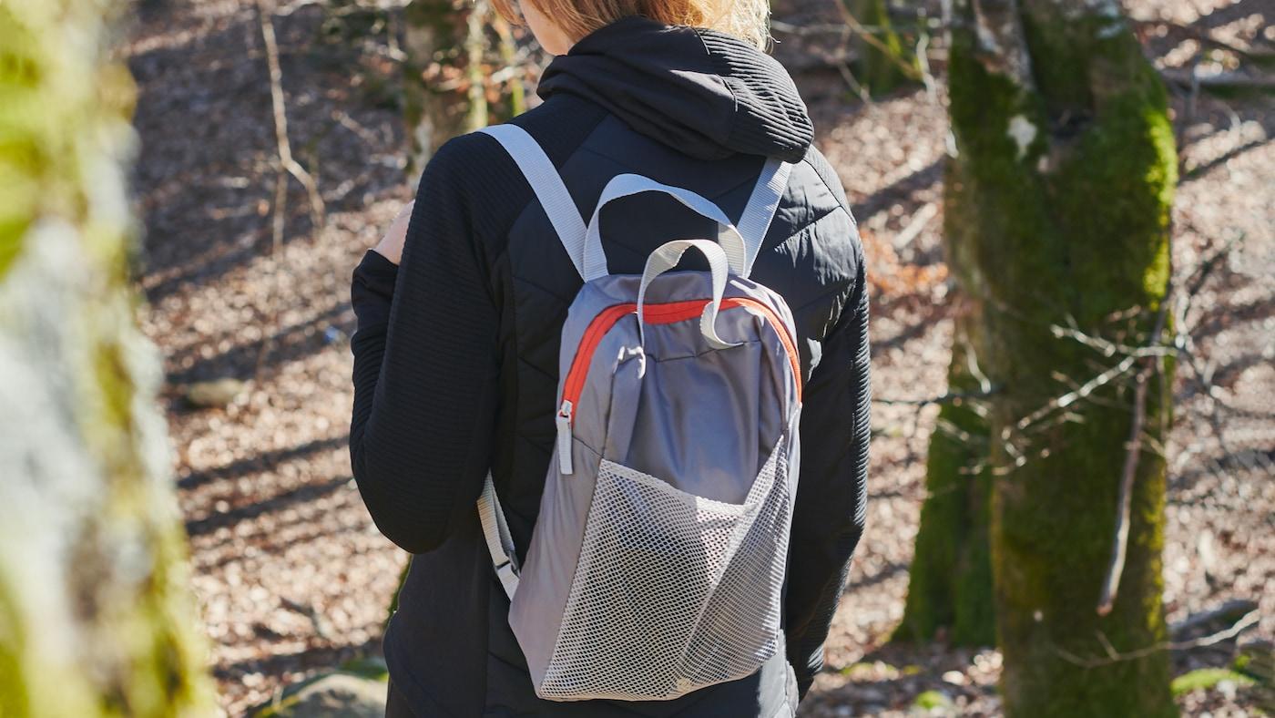Une personne se promène sur un flanc de colline éclairé par le soleil et parsemé d'arbres. Elle porte une veste et un sac à dos PIVRING gris clair.