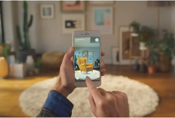 Une personne tient son téléphone dans une pièce et utilise une application pour voir à quoi une chaise jaune ressemblera.