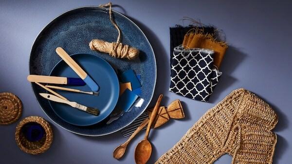 Une petite assiette bleue a été déposée sur une grande assiette bleue contenant des échantillons de peinture et des pinceaux, à côté d'échantillons de tissus et des cuillères en bois.
