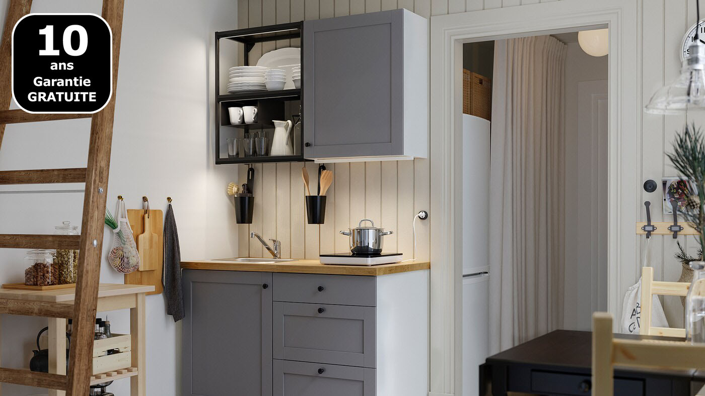 Une petite cuisine avec des étagères ouvertes en anthracite, des façades grises, un plan de travail en bois, une table noire et deux chaises en bois.