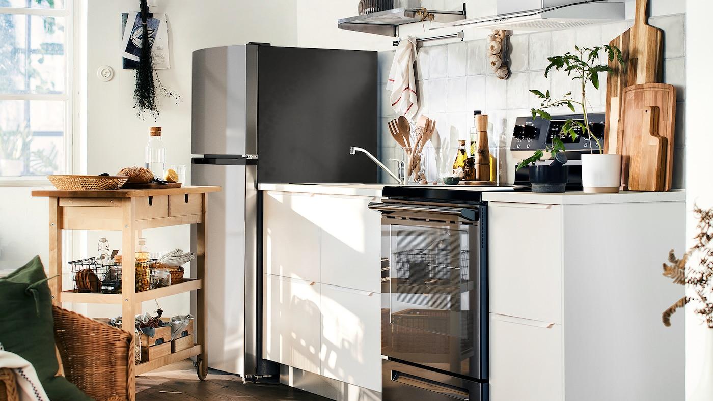 Une petite cuisine avec des façades d'armoires blanches, un réfrigérateur avec un congélateur dans la partie supérieure, un comptoir blanc et une desserte en bois.