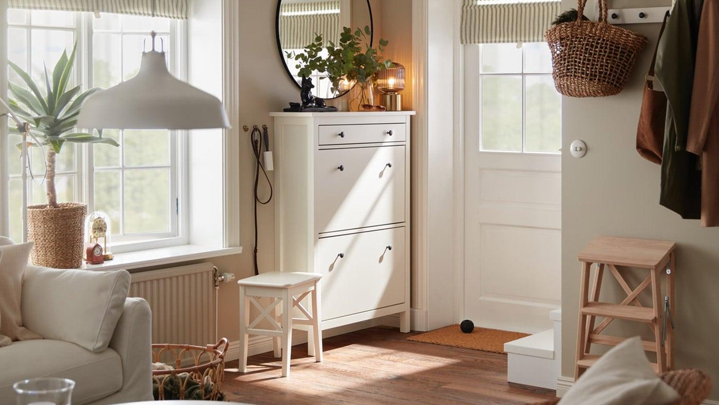 Une petite entrée avec une porte blanche, un range-chaussures blanc, un miroir rond et une étagère-patère blanche où sont suspendus des vestes et un parapluie.