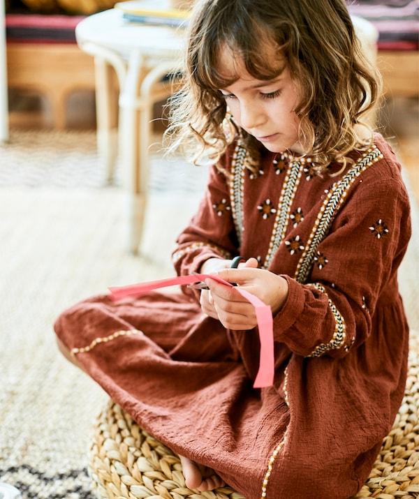 Une petite fille assise sur un pouf en rotin en train de découper une bande de papier.