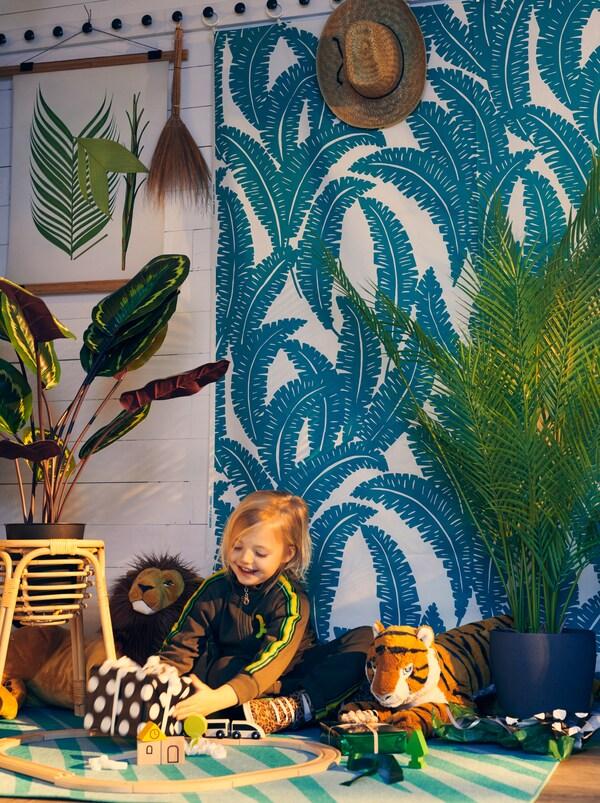 Une petite fille avec un cadeau emballé dans une pièce aux allures de jungle grâce aux plantes, au tissu UGGLEMOTT au mur et au tapis GRACIÖS.