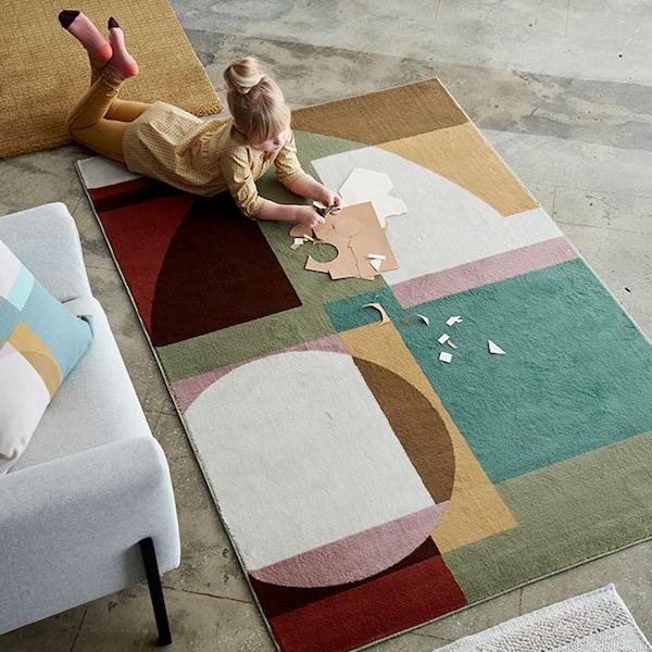 Une petite fille joue sur un tapis coloré au grand motif géométrique.
