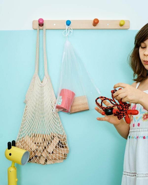 Une petite fille près d'un mur turquoise tient une corde à sauter, un sac-filet avec des morceaux de bois est suspendu à une rangée de crochets en bois.