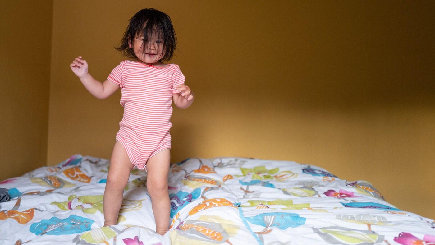 Une petite fille s'amuse à faire des bonds sur un lit, ses cheveux foncés recouvrant son visage.
