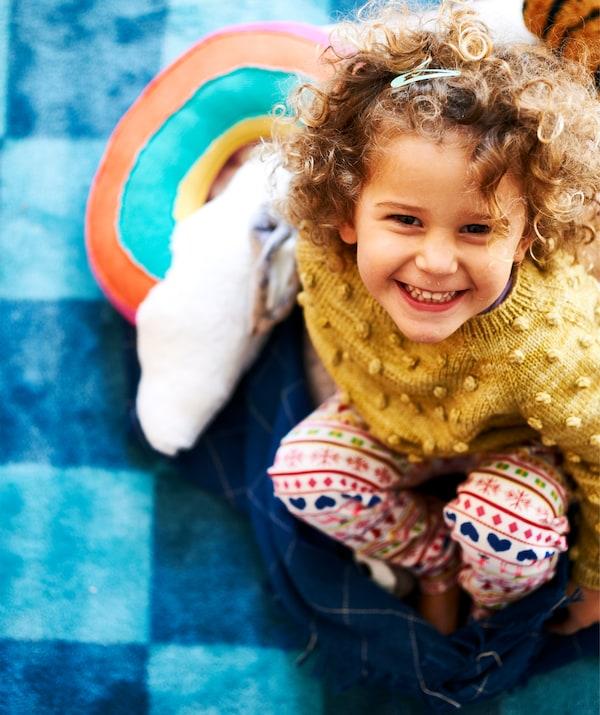 Une petite fille souriante assise sur un plaid bleu foncé sur un tapis à carreaux bleus.