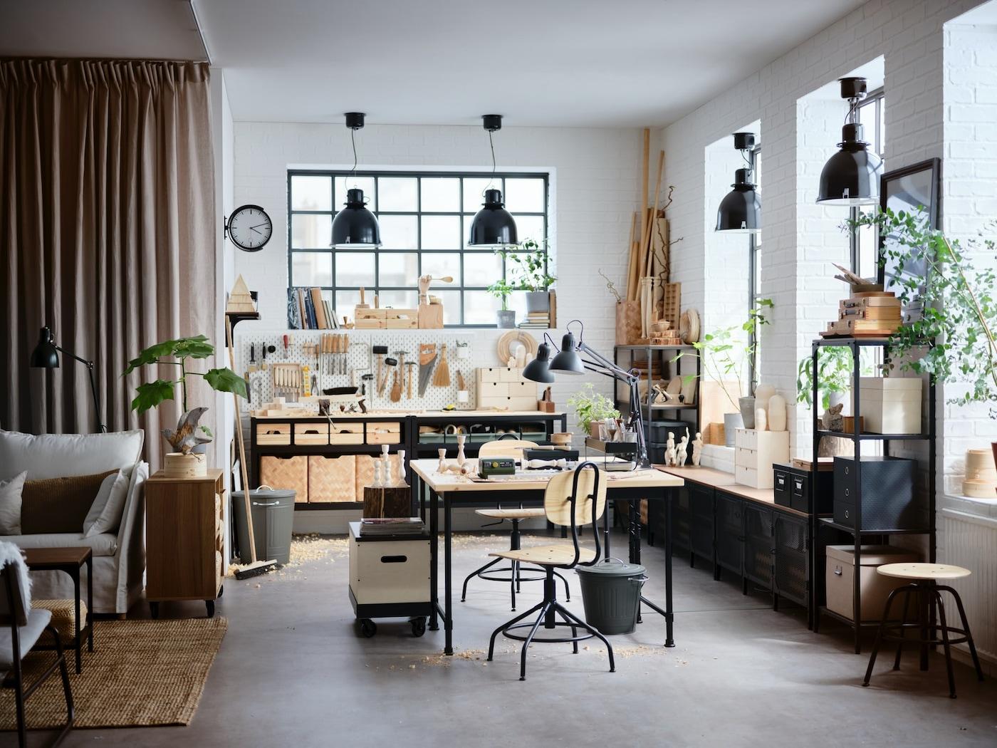 Une petite pièce avec un bureau vert, des étagères blanches, un lit banquette, une armoire ouverte et une suspension noire.