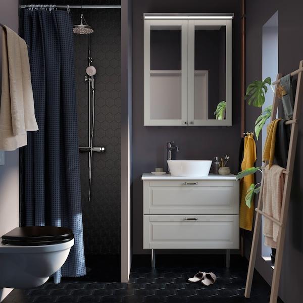 Une petite salle de bain gris foncé avec un meuble lavabo GODMORGON blanc, un plateau TOLKEN et un lavabo KATTEVIK.