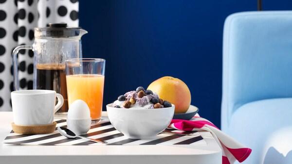 Une pièce aux murs bleus avec une table blanche dressée pour le petit-déjeuner avec un bol de céréales, une tasse, du café et un pamplemousse.