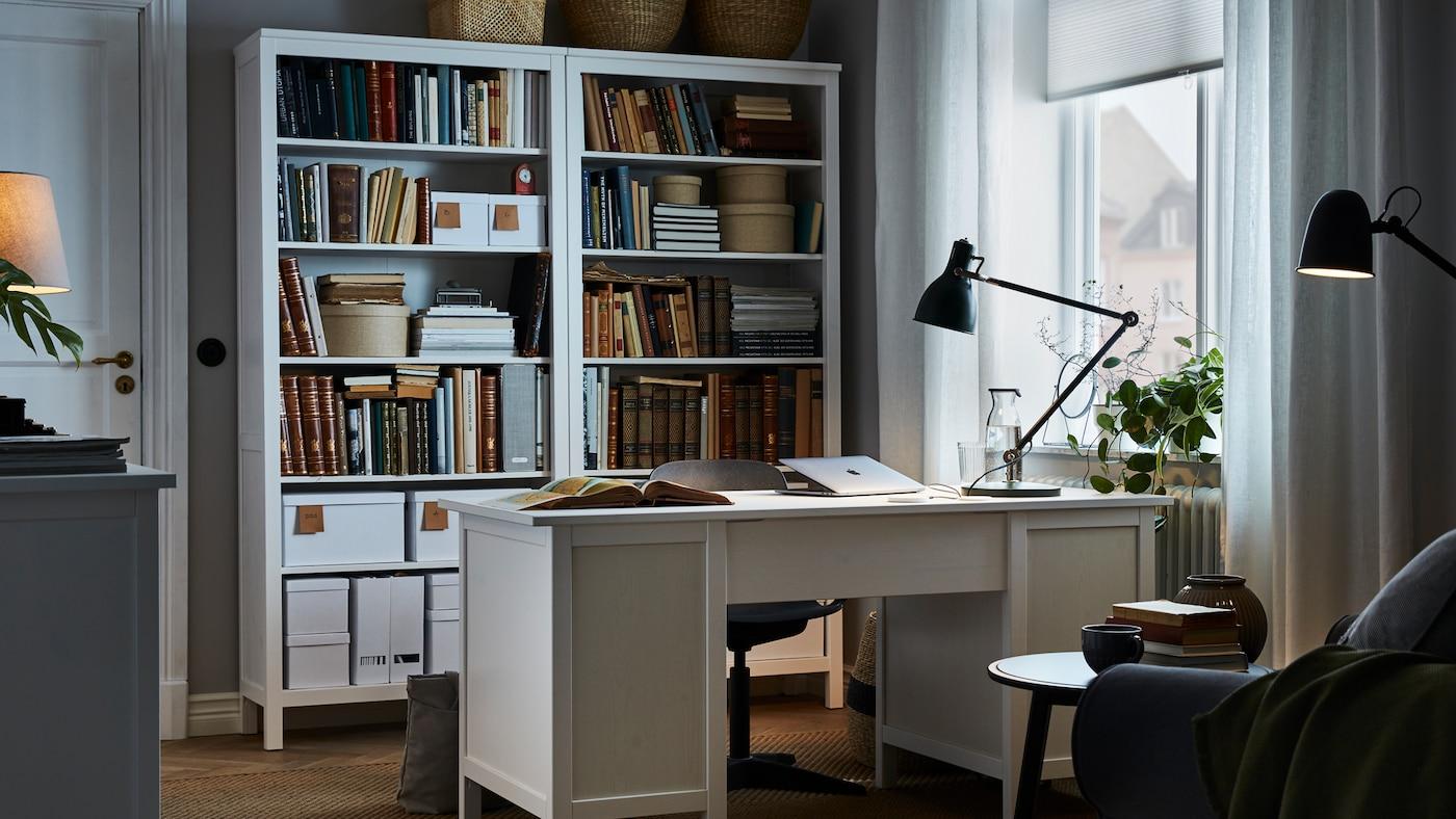 Une pièce avec un bureau blanc au centre, de hautes bibliothèques assorties derrière le bureau, et une lampe de travail verte sur le bureau.