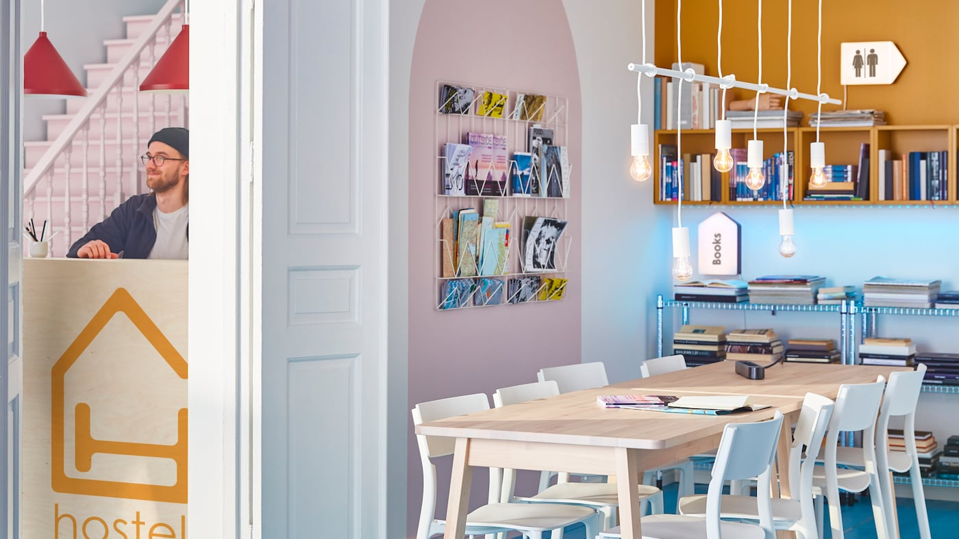 Une pièce avec une grande table en bois et des chaises blanches au milieu, et un espace de rangement mural avec des magazines et des livres.