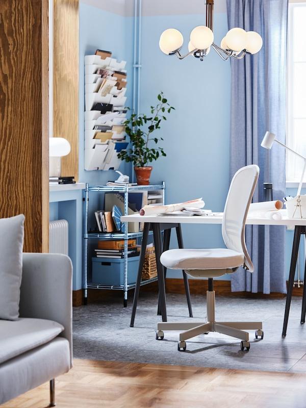 une pièce dans les tons bleus avec un bureau et une chaise de bureau grise claire