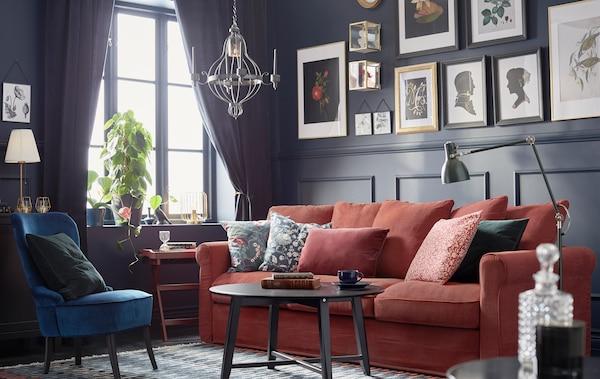 Une pièce de style traditionnel avec des panneaux muraux foncés, des œuvres d'art encadrées, un canapé HÄRLANDA rouge avec des coussins et une table basse KRAGSTA.