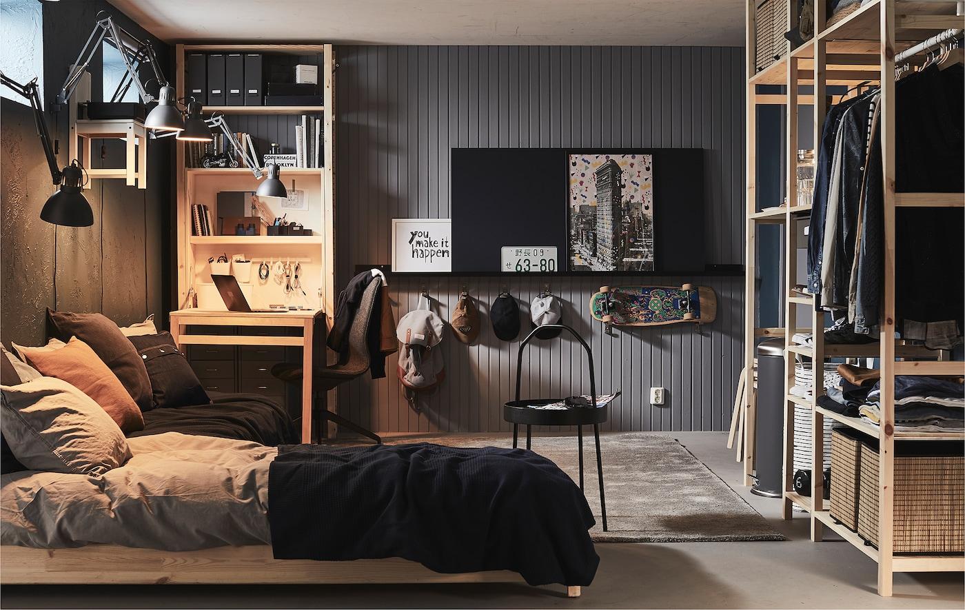 Une pièce meublée avec des fenêtres hautes, dans une cave ou un garage, aménagée d'un lit, d'un bureau et de rangements placés dans différentes étagères.