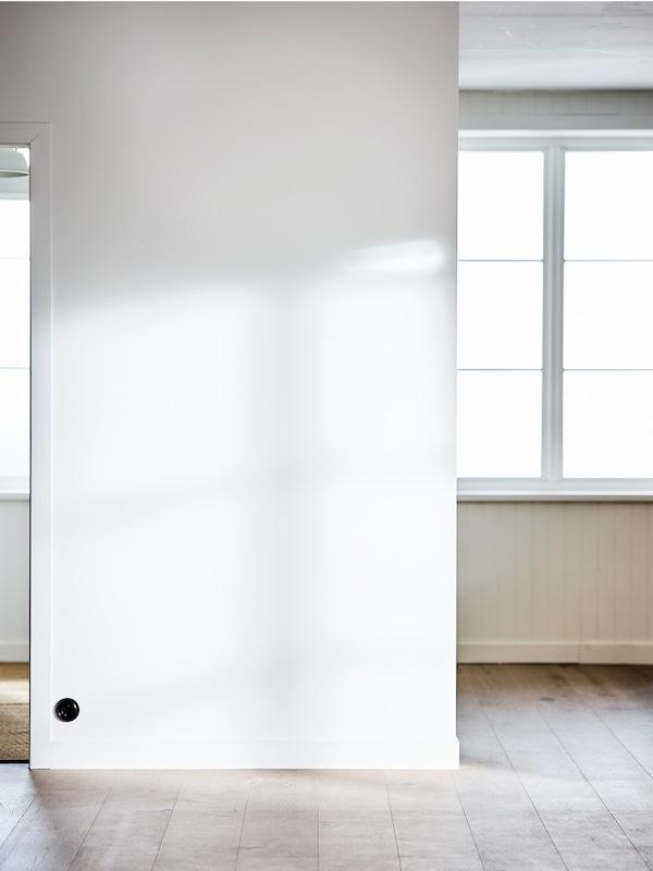 Une pièce vide avec une grande fenêtre, des murs peints en blanc et un plancher en bois blanchi.