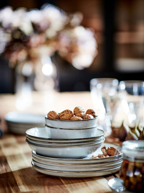 Une pile de bols et d'assiettes GLADELIG entourés de bocaux, de verres et de collations placés sur la surface en bois d'unetable.