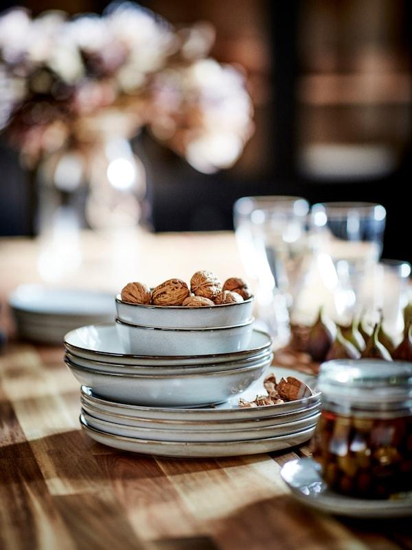 Une pile de bols et d'assiettes GLADELIG entourés de bocaux, de verres et de collations placés sur la surface en bois d'une table.