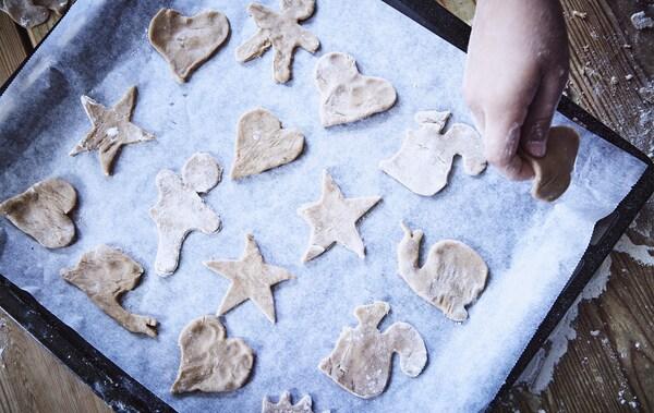 Une plaque de cuisson remplie de biscuits découpés dans la pâte.