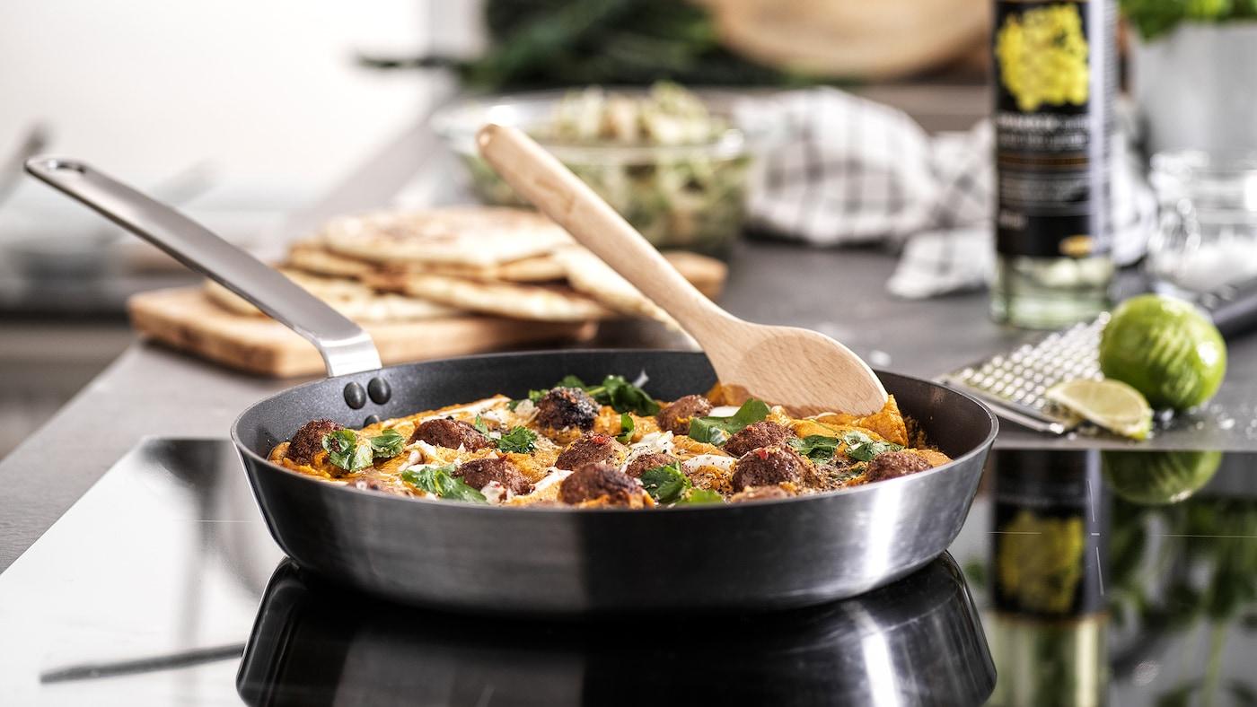 Une poêle avec un manche en acier inoxydable se trouve sur une table de cuisson et contient des boulettes de viande en sauce. Une cuillère en bois est posée sur le côté.