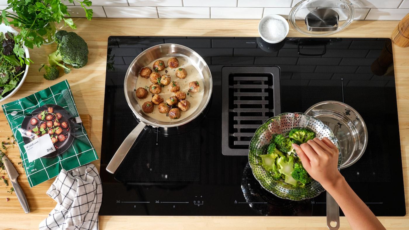 Une poêle fait cuire des boules de plantes HUVUDROLL en sauce sur une plaque à induction FÖRDELAKTIG à induction. A côté se trouve une passoire avec des brocolis.